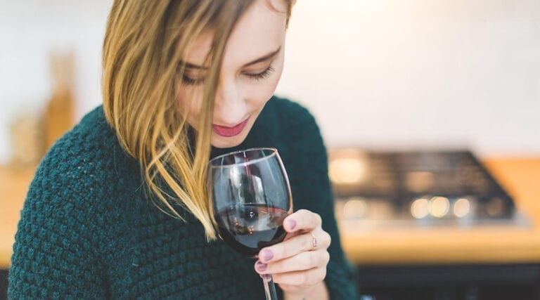 Young woman smelling red wine from a glass
