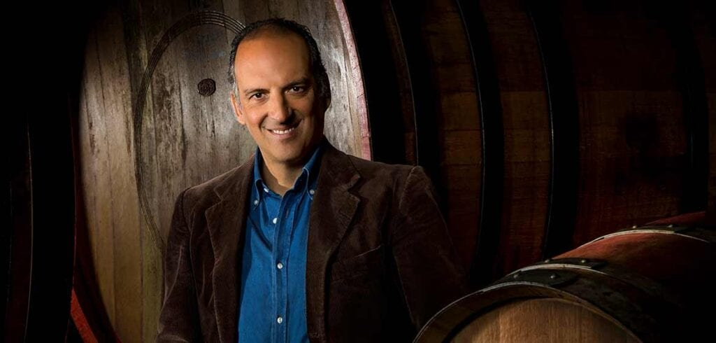 Wine producer Giovanni Folonari standing amidst barrels in a wine cellar in Tuscany, Italy. Copyright Angelo Trani