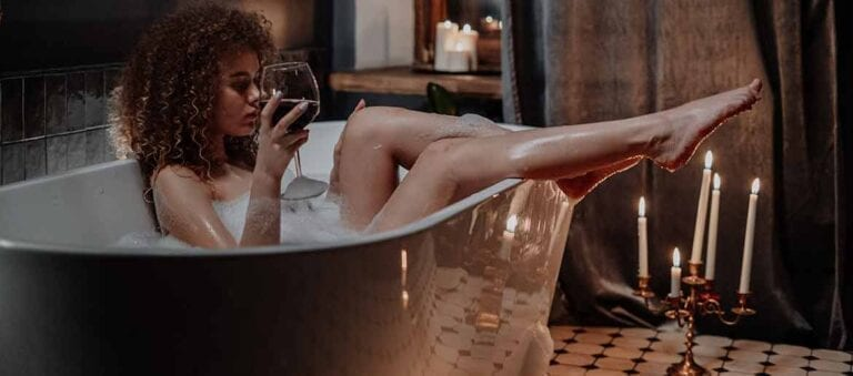 Woman in bathtub drinking red wine and showing legs