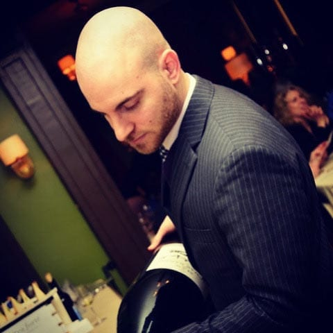 Sommelier Todd Lipman pouring a large bottle of wine in a restaurant