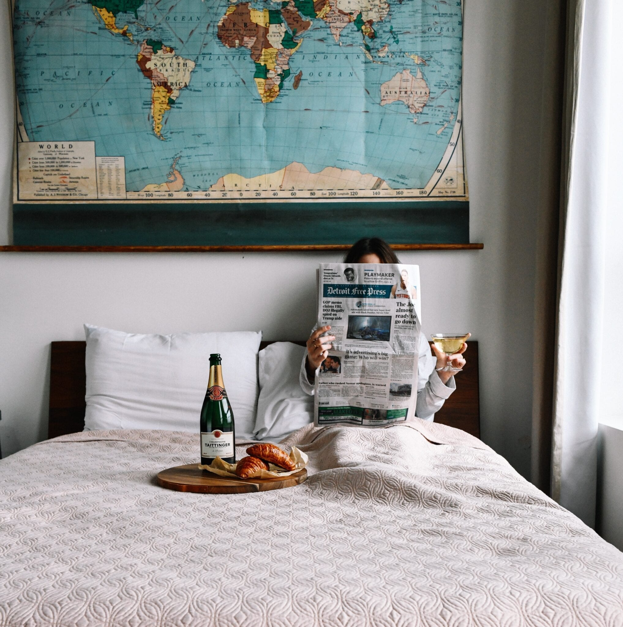Reading in bed with wine and travel map poster
