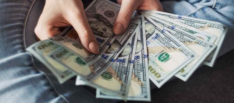 Hands holding 100 dollar bills cash